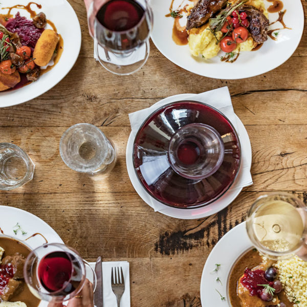 Wild und Wein, Esstisch mit Rotweinen und Weißweinen